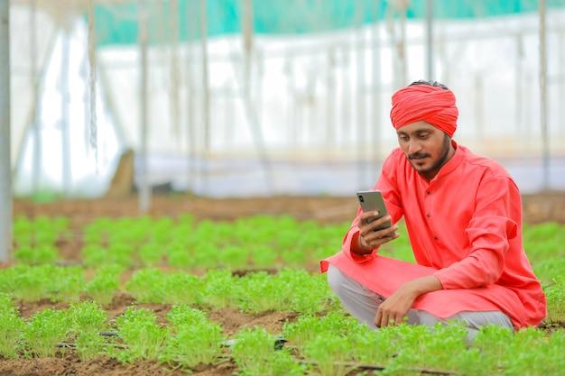 Jovem fazendeiro indiano usando smartphone em casa poli