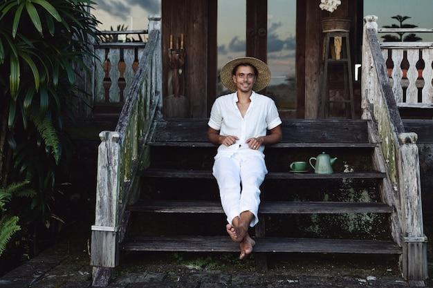 Jovem fazendeiro sentado na varanda de sua casa bebendo chá