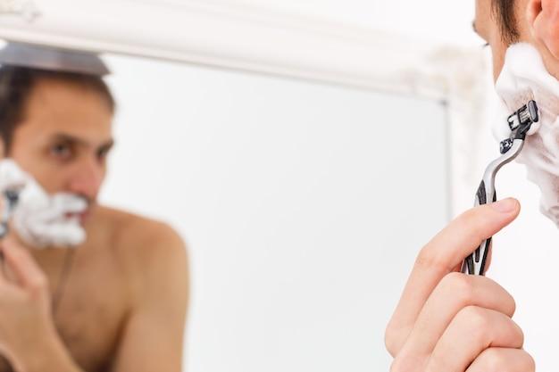 Jovem fazendo a barba no banho. ele está passando a navalha pela barba enquanto se olha no espelho