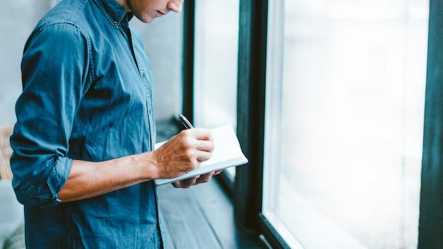 Jovem fazendo anotações em um caderno, perto da janela