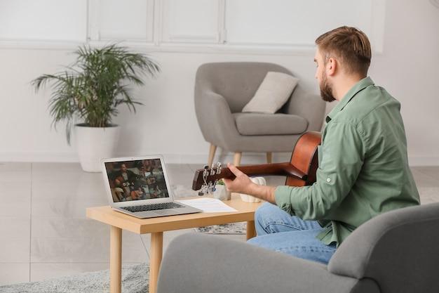 Jovem fazendo aulas de música online em casa