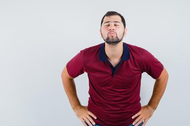 Jovem fazendo beicinho os lábios enquanto fecha os olhos em uma camiseta vermelha e parece pronto. vista frontal.