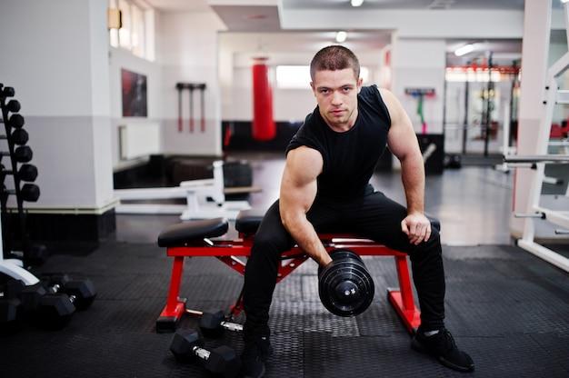 Jovem fazendo exercícios e trabalhando duro no ginásio e desfrutando de seu processo de treinamento.