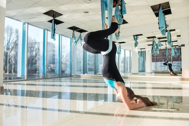 Jovem fazendo exercícios matinais usando ioga com mosca e alongamentos no treinamento físico