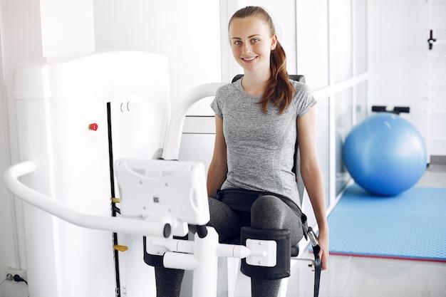 Jovem fazendo exercícios no simulador na sala de fisioterapia