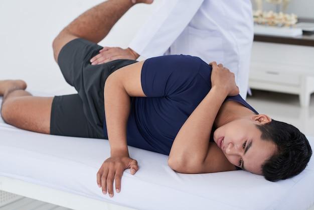 Jovem fazendo fisioterapia na clínica