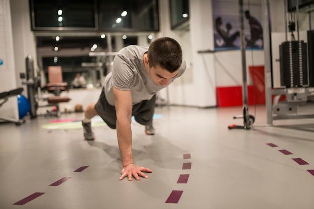 Jovem fazendo flexões por um lado no ginásio