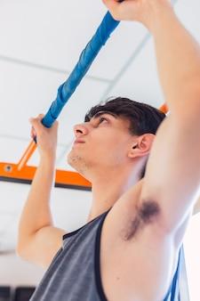 Jovem fazendo fortalecimento de braço na academia