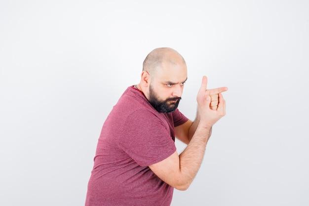 Jovem fazendo gesto de arma de tiro em t-shirt rosa e parecendo corajoso. .
