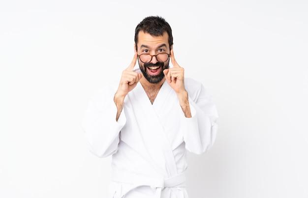 Jovem fazendo karatê sobre branco com óculos e surpreso