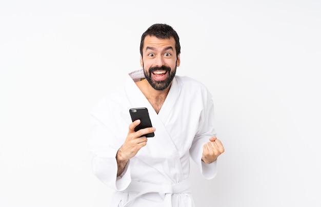 Jovem fazendo karatê sobre branco isolado surpreso e enviando uma mensagem
