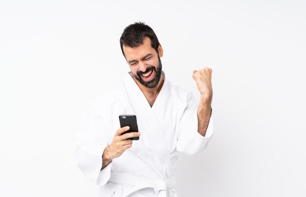Jovem fazendo karatê sobre fundo branco isolado com telefone em posição de vitória