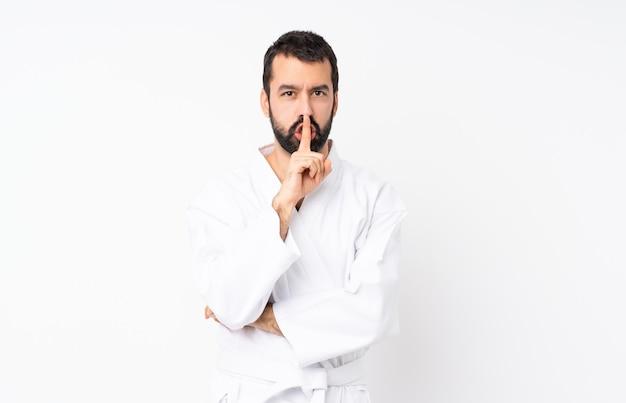 Jovem fazendo karatê sobre parede branca isolada, mostrando um sinal de gesto de silêncio colocando o dedo na boca