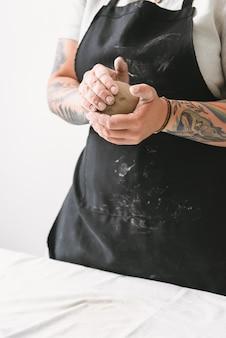 Jovem fazendo panela de barro na oficina de cerâmica