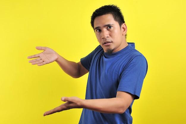 Jovem fazendo perguntas com as mãos levantadas, isoladas em fundo amarelo