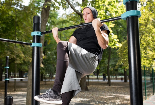 Jovem fazendo pull ups na barra horizontal ao ar livre, treino, conceito de esporte.