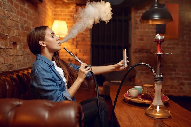 Jovem fazendo selfie com narguilé em bar, nuvem hipnotizante