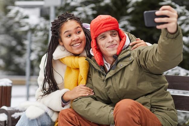 Jovem fazendo selfie retrato em seu celular com uma mulher, enquanto eles estão sentados no banco em winter park