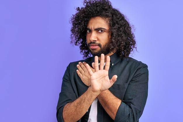 Jovem fazendo sinal de pare com a palma da mão, expressão de advertência com gesto negativo e sério no rosto isolado no espaço roxo