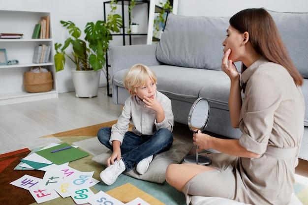 Jovem fazendo terapia da fala com um garotinho loiro