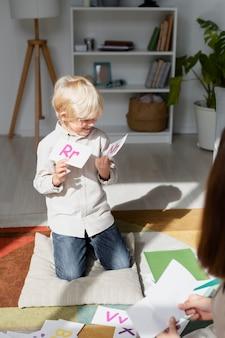 Jovem fazendo terapia da fala com um menino