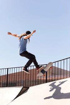 Jovem fazendo truque no skate completo