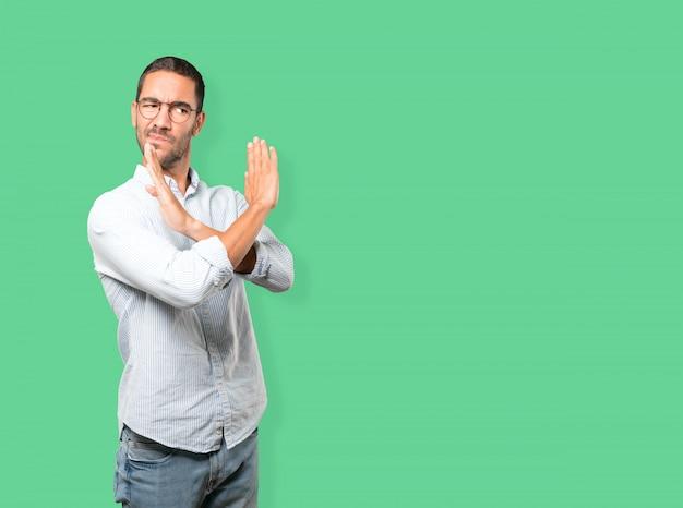 Jovem fazendo um gesto de não cruzar com os braços