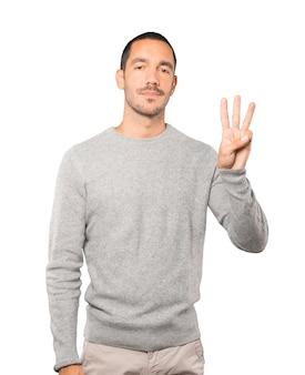 Jovem fazendo um gesto de número três
