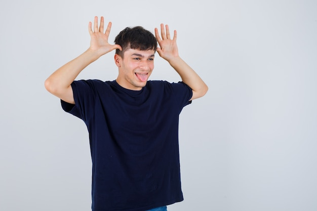 Jovem fazendo um gesto engraçado, mostrando a língua em uma camiseta preta e olhando divertido, vista frontal.