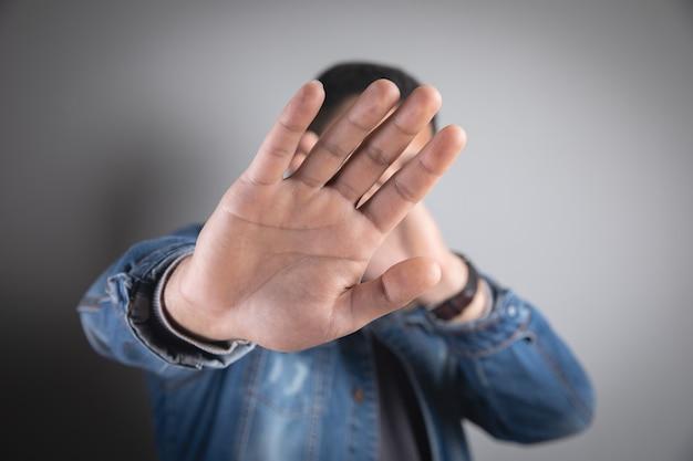 Jovem fazendo um sinal de pare com as mãos