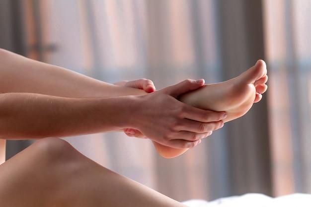 Jovem fazendo uma relaxante massagem nos pés em casa na cama depois de um longo e árduo dia de trabalho. terapia manual. dor no tratamento, fadiga e desconforto nas pernas