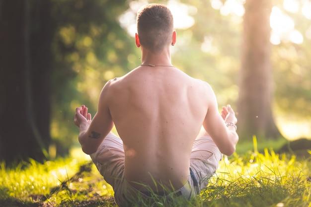 Jovem fazendo yoga na floresta.