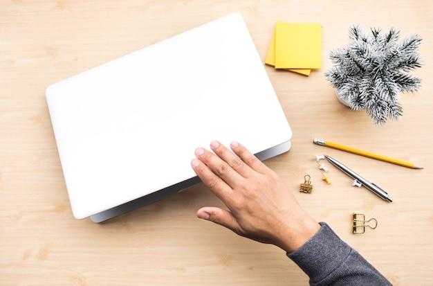 Jovem, fechando o laptop do computador com o objeto de acessórios no fundo da mesa de mesa de madeira.