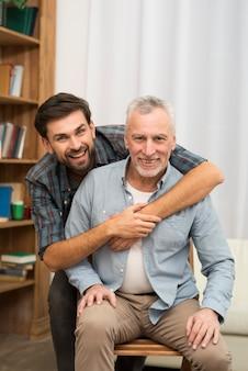 Jovem feliz, abraçando o homem envelhecido na cadeira
