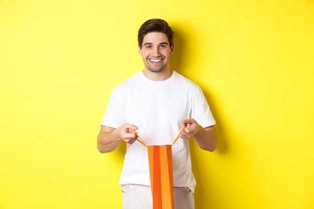 Jovem feliz abre a sacola de compras com um presente, sorrindo para a câmera, em pé contra um fundo amarelo.