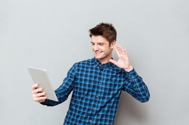 Jovem feliz acenando para os amigos pelo computador tablet