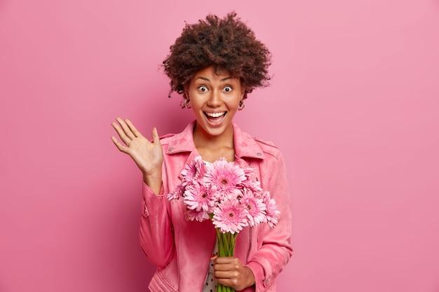 Jovem feliz afro-americana de cabelos cacheados recebe lindo buquê de gérberas para o feriado de primavera mantém a palma da mão levantada e usa uma jaqueta elegante isolada sobre a parede rosa do estúdio