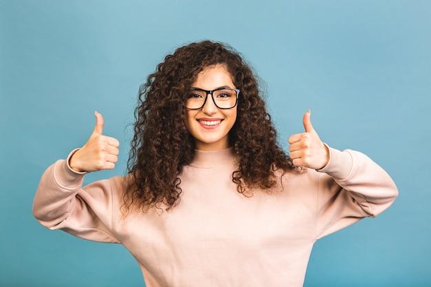 Jovem feliz alegre mulher cacheada aparecendo polegar isolado sobre fundo azul.