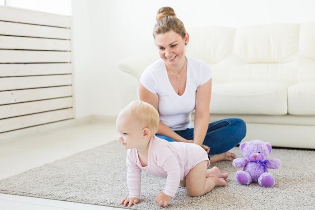 Jovem feliz amorosa mãe e sua filha bebê está jogando. cuidado materno. puericultura.