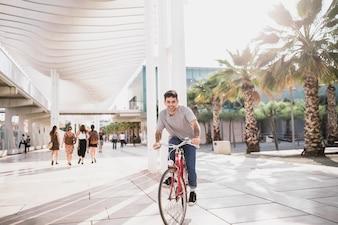 Jovem feliz andando de bicicleta na calçada