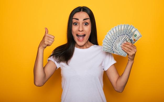 Jovem feliz animada linda mulher emocionalmente olhando para a câmera com muito dinheiro nas mãos e se divertindo isolado em um fundo amarelo