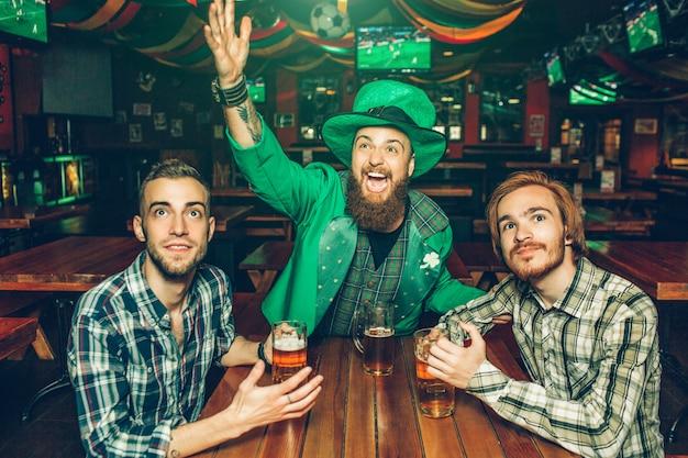 Jovem feliz animado em terno verde, acenando com as mãos e alcançar a frente. outros dois homens sentam-se na tabu e seguram canecas de cerveja.