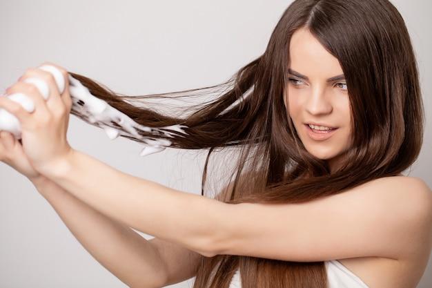 Jovem feliz aplicando condicionador de cabelo no banheiro