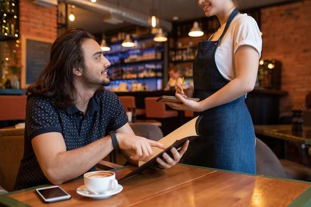 Jovem feliz apontando para o menu enquanto faz o pedido para a garçonete em pé na frente dele e fazendo anotações no bloco de notas