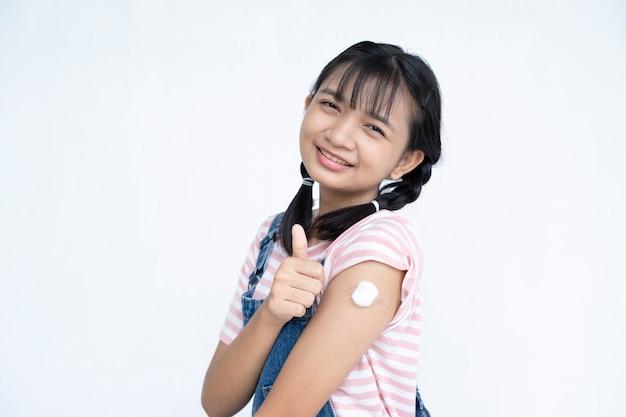 Jovem feliz após a vacinação menina asiática no conceito médico do estudante de fundo branco