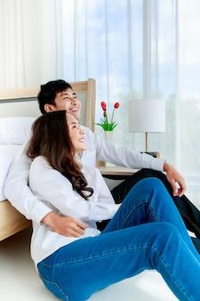 Jovem feliz atraente casal asiático abraçando sentados juntos no chão no quarto, olhando para o céu azul vista da janela através da cortina branca. conceito de amor e relacionamento feliz.