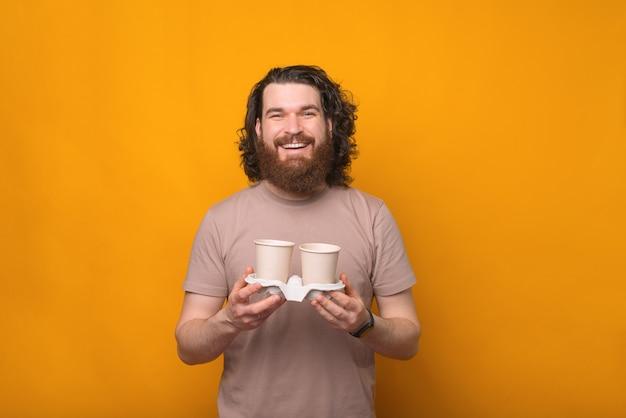 Jovem feliz barbudo com cabelo comprido segurando duas xícaras de café sobre amarelo