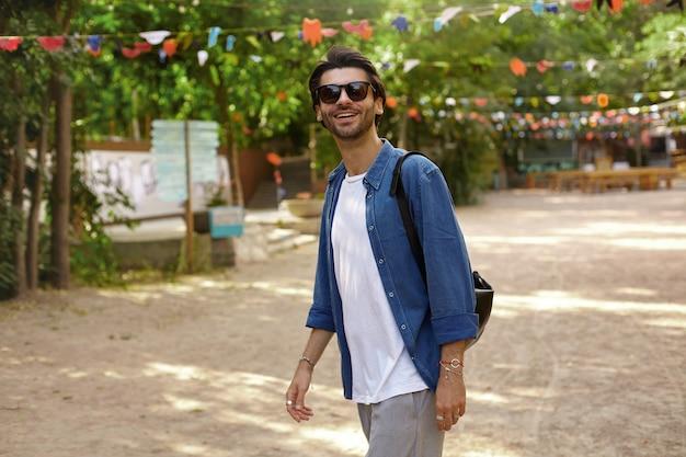 Jovem feliz barbudo com cabelo escuro caminhando pelo parque verde em um dia ensolarado e quente, usando roupas casuais e óculos escuros, e de bom humor