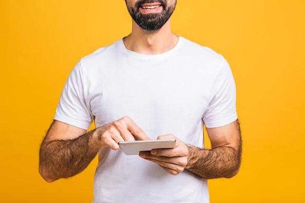 Jovem feliz barbudo homem em pé casual e usando tablet isolado sobre fundo amarelo. fechar-se.