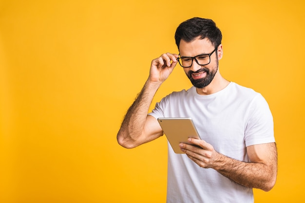 Jovem feliz barbudo homem em pé casual e usando tablet isolado sobre fundo amarelo.